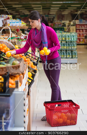 Smiling Woman Buying Dairy Products In Supermarket stock photo, Beautiful Young Woman Shopping For Fruits And Vegetables In Produce Department Of A Grocery Store - Supermarket - Shallow Deep Of Field by Jasminko Ibrakovic