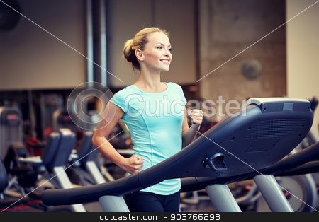 smiling woman exercising on treadmill in gym stock photo, sport, fitness, lifestyle, technology and people concept - smiling woman exercising on treadmill in gym by Syda Productions