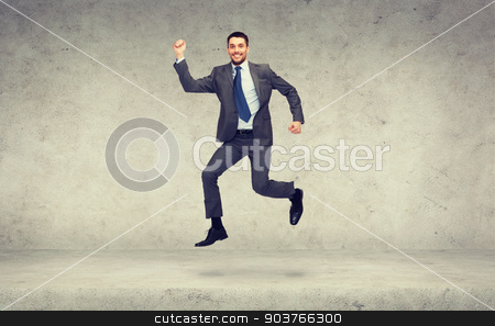 smiling businessman jumping stock photo, business and education concept - smiling businessman jumping by Syda Productions