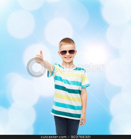 smiling cute little boy in sunglasses stock photo, happiness, summer, childhood, gesture and people concept - smiling cute little boy in sunglasses over blue background showing thumbs up by Syda Productions