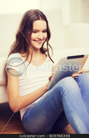 smiling teenage girl with tablet pc at home stock photo, home, technology and internet concept - smiling teenage girl sitting ong the floor with tablet pc computer at home by Syda Productions