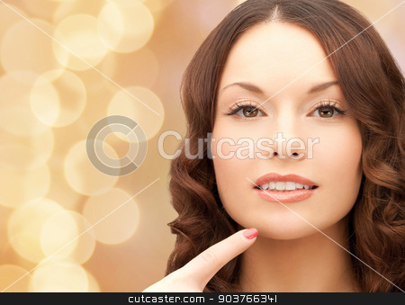beautiful young woman pointing finger to her chin stock photo, beauty, people and health concept - beautiful young woman pointing finger to her chin over beige lights background by Syda Productions