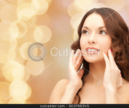 beautiful young woman face stock photo, beauty, people and health concept - beautiful young woman touching her face over beige lights background by Syda Productions