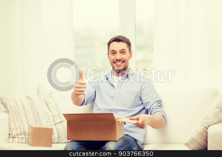 man with cardboard boxes at home showing thumbs up stock photo, post, home and lifestyle concept - smiling man with cardboard boxes at home showing thumbs up by Syda Productions