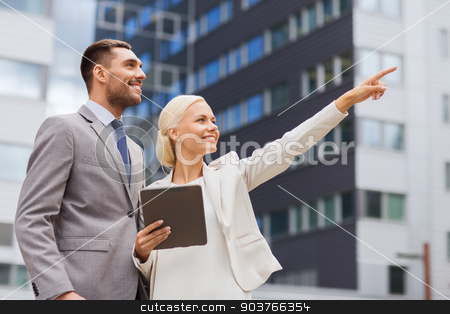 smiling businessmen with tablet pc outdoors stock photo, business, partnership, technology and people concept - smiling businessman and businesswoman with tablet pc computer over office building by Syda Productions