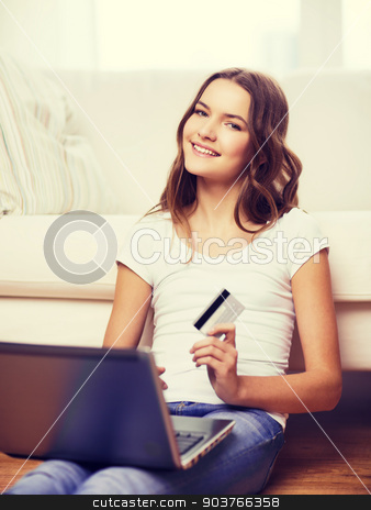 smiling teenage girl with laptop and credit card stock photo, online shopping, banking and technology concept - smiling teenage girl with laptop computer and credit card at home by Syda Productions