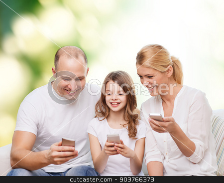 happy family with smartphones stock photo, family, summer, technology and people - smiling mother, father and little girl with smartphones over green background by Syda Productions