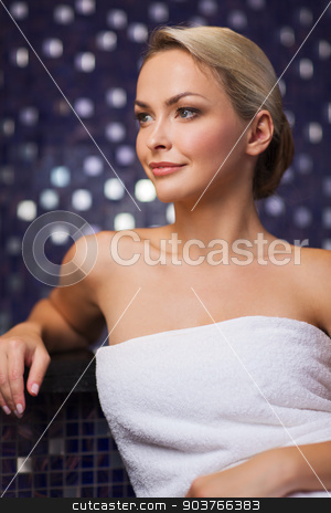 beautiful young woman sitting in bath towel stock photo, people, beauty, spa, healthy lifestyle and relaxation concept - beautiful young woman sitting in bath towel by Syda Productions