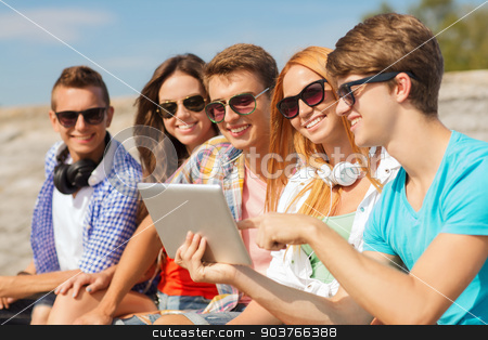 group of smiling friends with tablet pc outdoors stock photo, friendship, leisure, summer and people concept - group of smiling friends with tablet pc computer sitting outdoors by Syda Productions