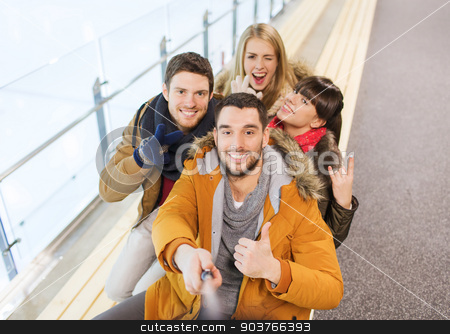 happy friends taking selfie on skating rink stock photo, people, friendship, technology and leisure concept - happy friends taking selfie with camera or smartphone and selfie stick on skating rink by Syda Productions