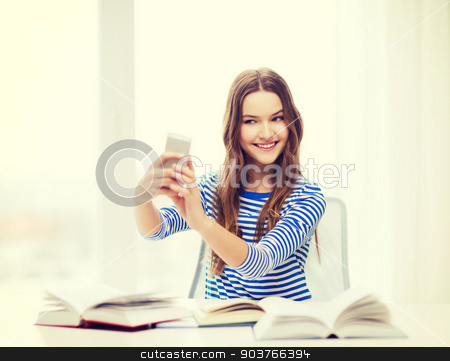 smiling student girl with smartphone and books stock photo, education, technology and home concept - happy smiling student girl with smartphone and books at home by Syda Productions