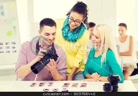 smiling team with photocamera working in office stock photo, business, education, photography, office and startup concept - smiling creative team with photocamera working in office by Syda Productions