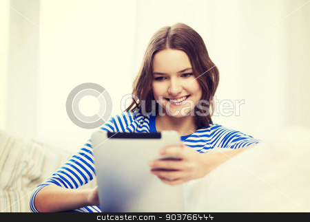 smiling teenage girl with tablet pc at home stock photo, home, technology and internet concept - smiling teenge girl lying on the couch with tablet pc computer at home by Syda Productions