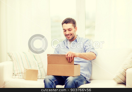 man with cardboard boxes at home stock photo, post, home and lifestyle concept - smiling man with cardboard boxes at home by Syda Productions