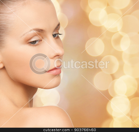 beautiful young woman face stock photo, beauty, people and health concept - beautiful young woman face over beige lights background by Syda Productions