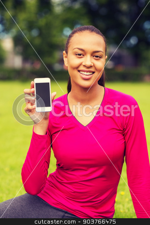 smiling african american woman with smartphone stock photo, fitness, park, technology and sport concept - smiling african american woman showing smartphone outdoors by Syda Productions