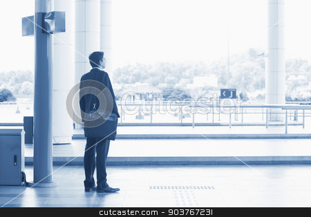Indian business man waiting bus  stock photo, Rear view full body Asian Indian business man waiting bus at public bus station, in blue tone. by szefei