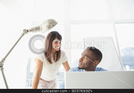 Casual coworkers smiling at each other stock photo, Casual coworkers smiling at each other in the office by Wavebreak Media