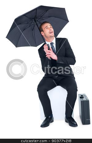 Smiling businessman under umbrella sitting on cube stock photo, Smiling businessman under umbrella sitting on cube on white background by Wavebreak Media