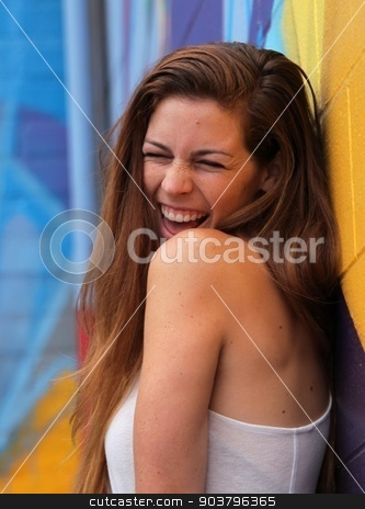 Young Woman stock photo, Young woman standing in front of a colorful background and laughing. by Henrik Lehnerer