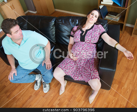 Exhaused Expecting Woman and Husband stock photo, Exhausted pregnant female sitting on couch together by Scott Griessel