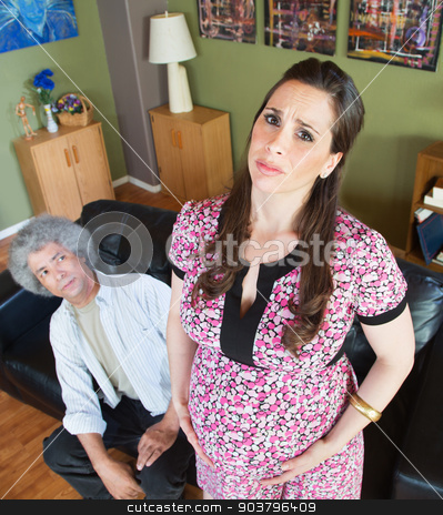 Miserable Pregnant Woman with Husband stock photo, Husband looking at miserable pregnant wife holding belly by Scott Griessel