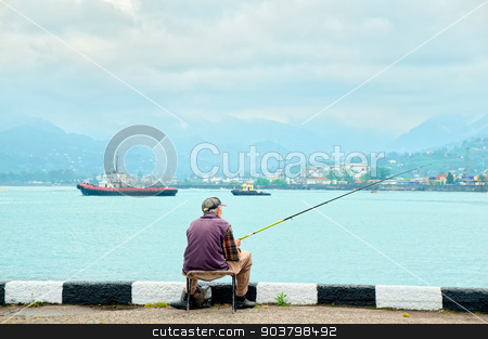 fisherman fishing in the port. stock photo, Old georgian fisherman fishing in the sea port. by MaStudio