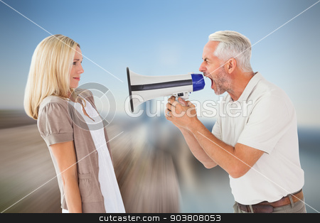 Composite image of angry man shouting at girlfriend through mega stock photo, Angry man shouting at girlfriend through megaphone against large rock overlooking foggy city by Wavebreak Media