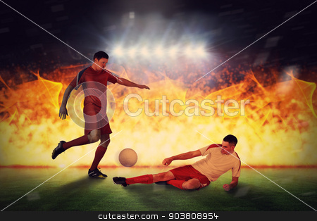Composite image of football players tackling for the ball stock photo, Football players tackling for the ball against football pitch under spotlights by Wavebreak Media