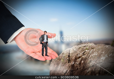 Composite image of serious businessman with hand on hip in large stock photo, Serious businessman with hand on hip in large hand against large rock overlooking foggy city by Wavebreak Media