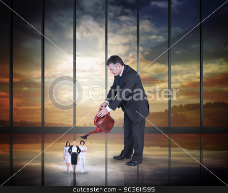 Composite image of mature businessman watering tiny business wom stock photo, Mature businessman watering tiny business women against room with large window looking on landscape by Wavebreak Media