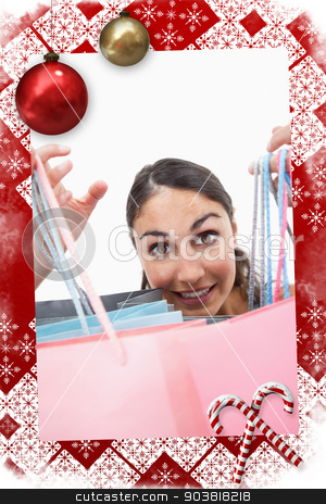 Composite image of portrait of a cheerful woman showing shopping stock photo, Portrait of a cheerful woman showing shopping bags against christmas themed page by Wavebreak Media