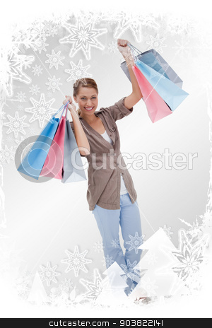 Composite image of happy woman with her shopping bags stock photo, Happy woman with her shopping bags against christmas frame by Wavebreak Media