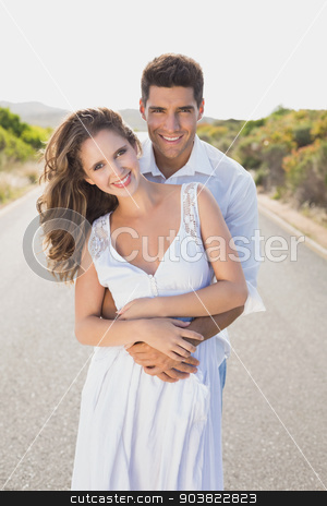 Loving couple standing on countryside road stock photo, Portrait of a loving young couple standing on countryside road by Wavebreak Media