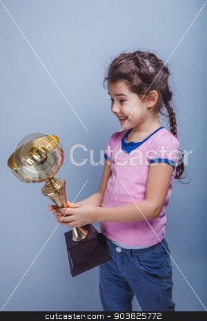 girl child 6 years of European appearance  holds a  cup in  his  stock photo, girl child 6 years of European appearance  holds a  cup in  his  hands,  happiness  on a gray  background by maxximmm