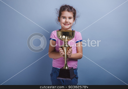 girl child 6 years of European appearance holds a cup in his han stock photo, girl child 6 years of European appearance holds a cup in his hands,  happiness,  reward  and joy on a gray background by maxximmm
