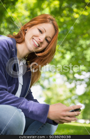 Pretty redhead relaxing in the park sending a text stock photo, Pretty redhead relaxing in the park sending a text on a sunny day by Wavebreak Media