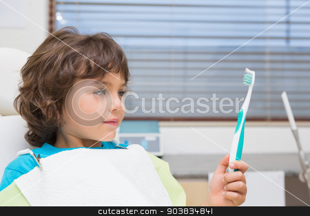 Little boy in dentists chair holding toothrbrush stock photo, Little boy in dentists chair holding toothrbrush at the dental clinic by Wavebreak Media