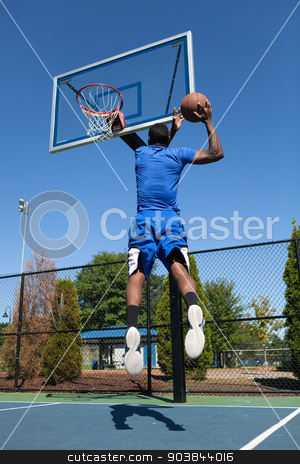 Slam Dunk Basketball stock photo, Young basketball player driving to the hoop for a high flying slam dunk. by Todd Arena