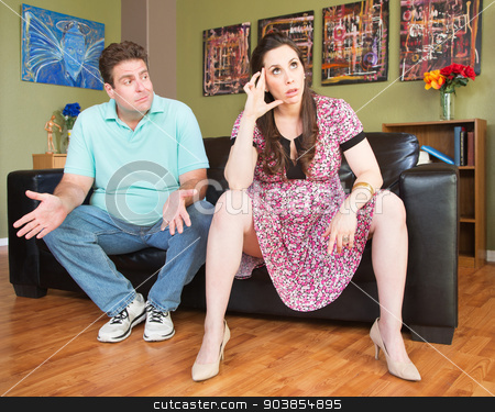Frustrated Expecting Parents stock photo, Frustrated man with annoyed expecting mother on sofa by Scott Griessel