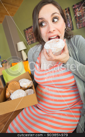 Messy Pregnant Woman Eating stock photo, Happy pregnant woman making a mess eating donuts by Scott Griessel