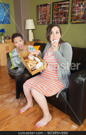 Expecting Woman Eating Sweets stock photo, Barefoot pregnant woman with surprised partner eating donuts by Scott Griessel