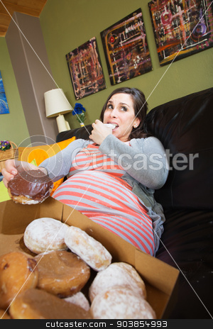 Pregnant Woman Eating Donuts stock photo, Embarrassed pregnant female pigging out on donuts by Scott Griessel