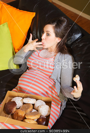 Donut Eating Pregnant Woman on Sofa stock photo, Pregnant woman with box of donuts licking her fingers by Scott Griessel