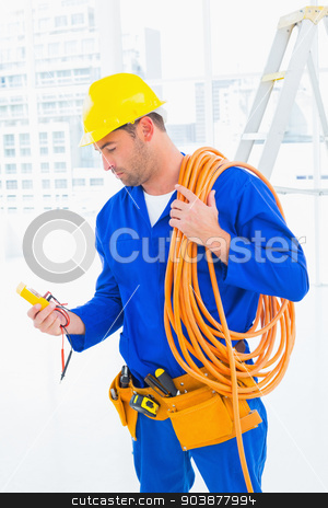 Electrician reading multimeter in bright office stock photo, Male electrician with wire roll looking at reading multimeter in bright office by Wavebreak Media