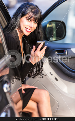 Pretty Woman Sitting in Car stock photo, Attractive business woman with smart phone sitting in automobile by Scott Griessel