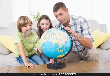 Family exploring globe stock photo, Father and children exploring globe in living room by Wavebreak Media