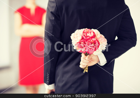 man hiding bouquet of flowers stock photo, man hiding bouquet of flowers behind his back. by Syda Productions
