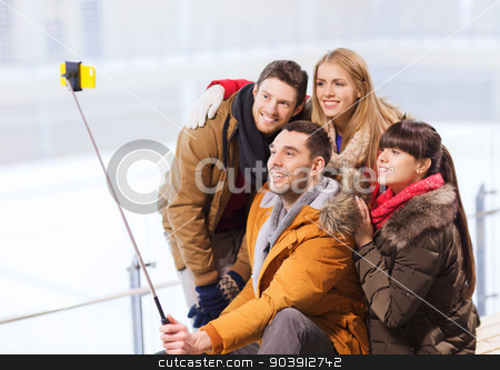 happy friends with smartphone on skating rink stock photo, people, friendship, technology and leisure concept - happy friends taking picture with smartphone selfie stick on skating rink by Syda Productions