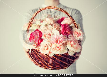 man holding basket full of flowers stock photo, close up of man holding basket full of flowers. by Syda Productions